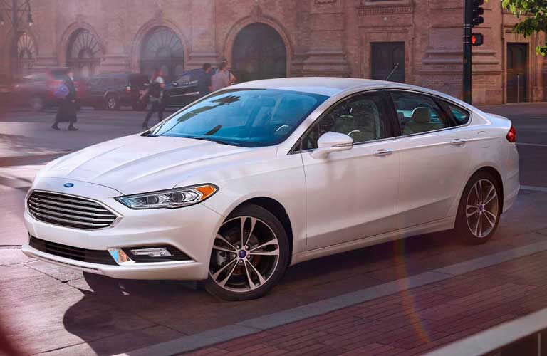 2017 Ford Fusion driving on an empty city road near a tree
