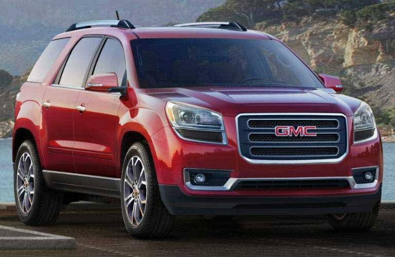 2016 GMC Acadia parked in front of a body of water by a cliff