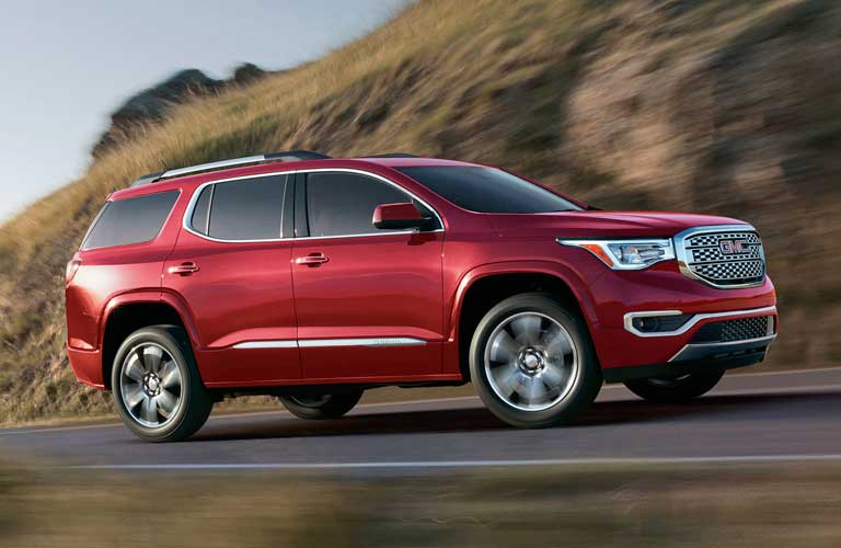 2017 GMC Acadia driving up a hill by a mountain