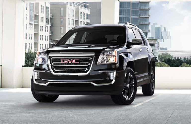2017 GMC Terrain parked in a parking lot overlooking a city with tall buildings
