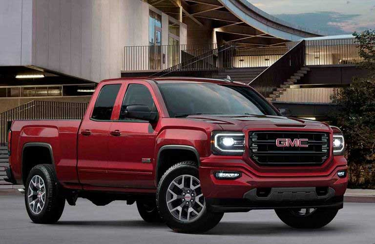 Side profile of the 2018 GMC Sierra 1500 parked in front of a building with stairs