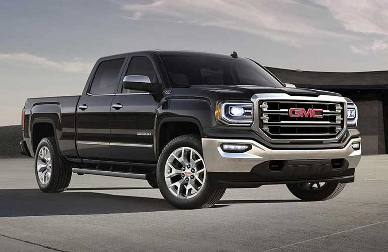 2017 GMC Sierra 1500 parked in front of a building with a glass panel