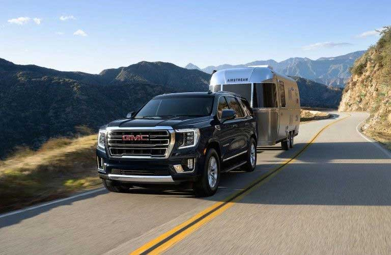 Front driver angle of a black 2020 GMC Yukon towing a trailer