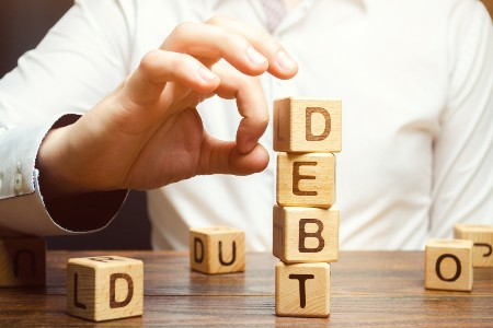 "Person knocking over a stack of wooden blocks that spell the word ""debt"""