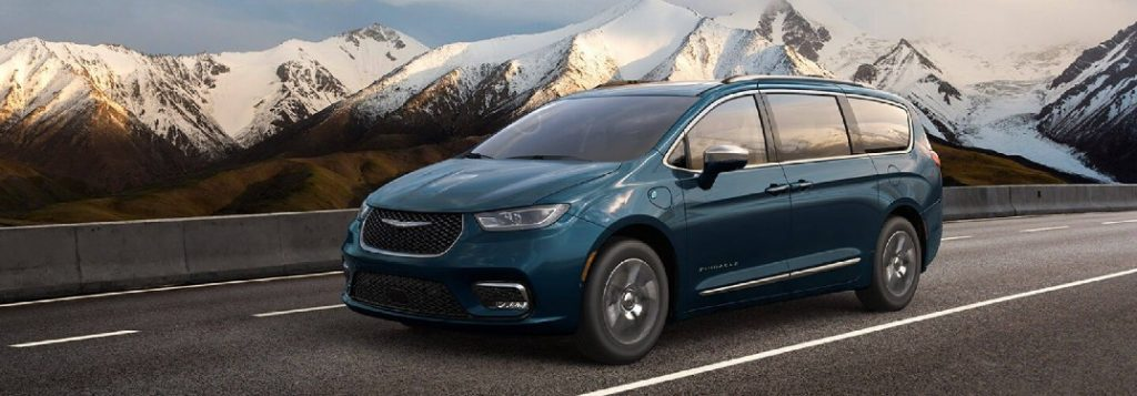 Front driver angle of a blue 2021 Chrysler Pacifica driving on a road with snowy mountains in the background