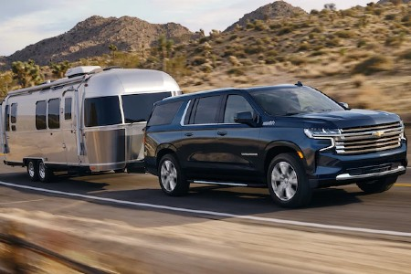 Front passenger angle of a blue 2021 Chevrolet Suburban towing a trailer