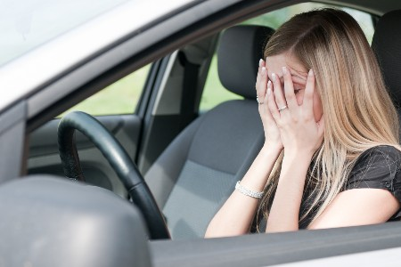 Unhappy woman in the driver seat of a car
