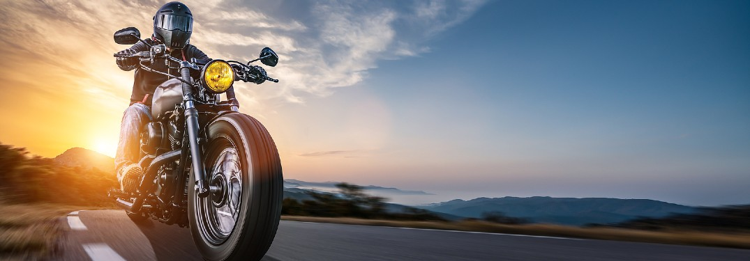 Motorcycle driving on a road with a sunset in the background