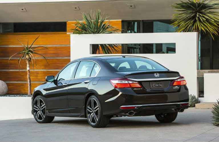 Rear quarter profile of the 2017 Honda Accord in front of a building with palm trees
