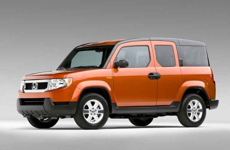 Front driver angle of an orange 2011 Honda Element on a grey background