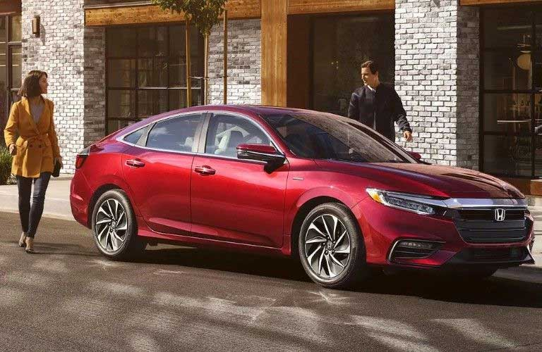 Front passenger angle of a red 2020 Honda Insight parked on the side of a street with a couple walking around it