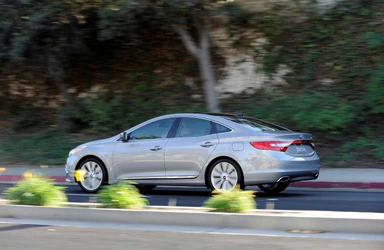 Rear driver angle of a silver 2017 Hyundai Azera driving on a road