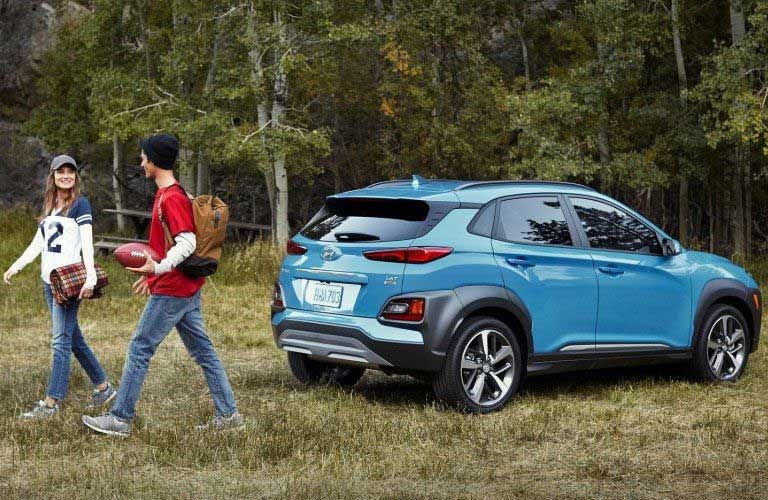 Rear passenger angle of a blue 2020 Hyundai Kona parked on grass with a happy couple walking away from it