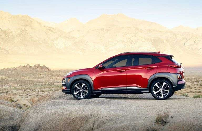 Driver angle of a red 2020 Hyundai Kona parked on a flat rock with a desert and mountains in the background