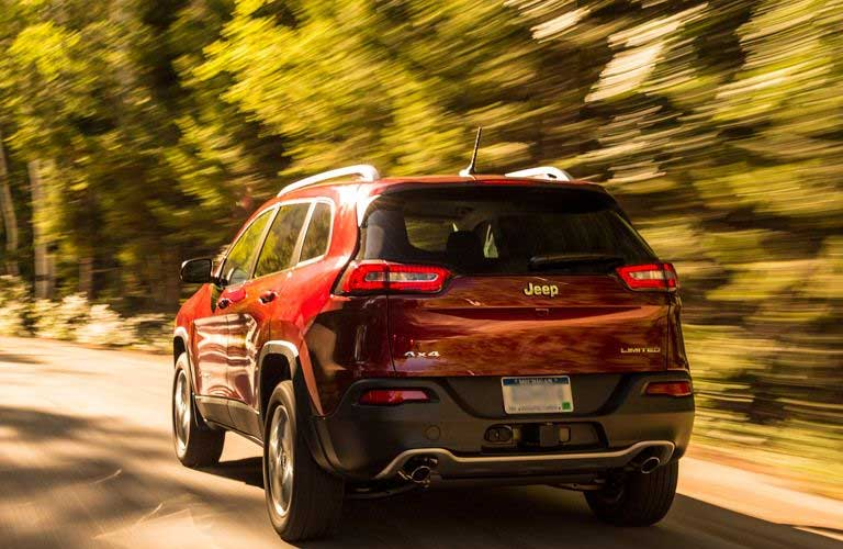 Rear profile of the 2016 Jeep Cherokee driving on a highway past a copse of trees