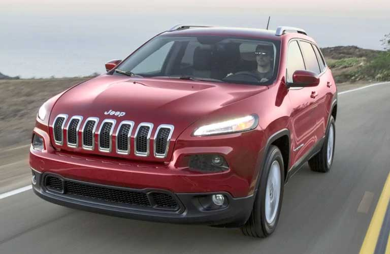 Front quarter profile of the 2016 Jeep Cherokee driving on a empty highway with hills and mountains