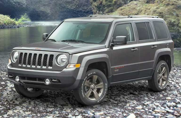 Jeep Patriot parked on rocks by a stream