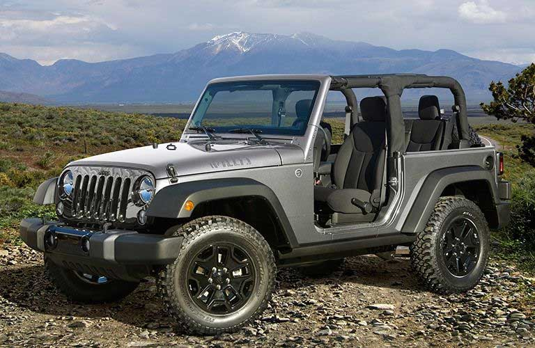Front quarter profile of the 2017 Jeep Wrangler with the top down by a mountain