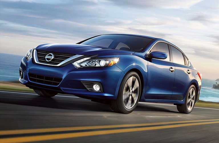 Side profile of the 2017 Nissan Altima driving on a highway by a body of water