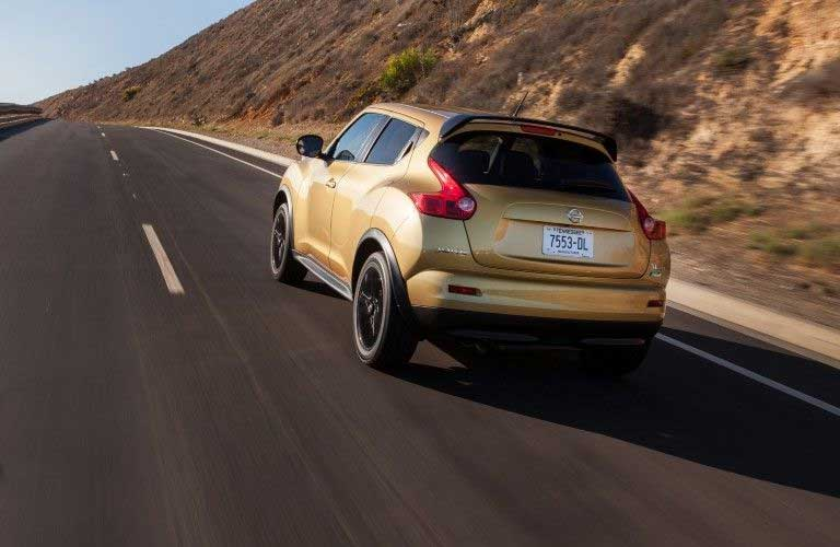 Rear driver angle of a tan 2013 Nissan JUKE driving on a road