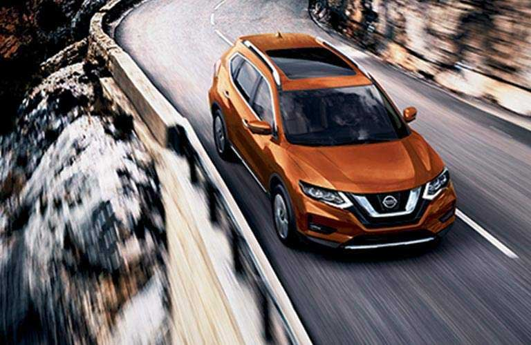 2017 Nissan Rogue driving on a mountain with curving roads