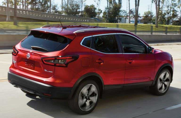 Rear passenger angle of a red 2020 Nissan Rogue Sport driving on a road