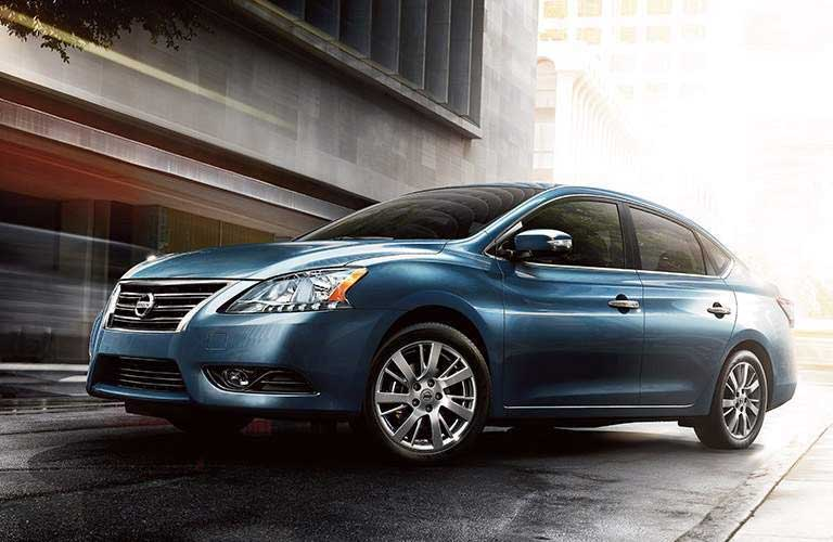2016 Nissan Sentra parked outside a modern glass and concrete building