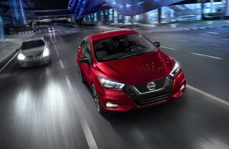 Front passenger angle of a red 2020 Nissan Versa driving in a city