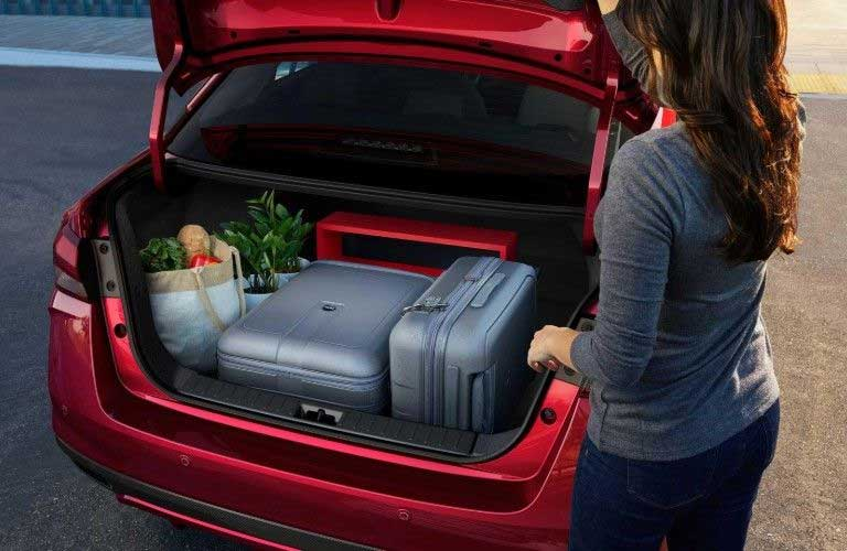 Rear passenger angle of a red 2020 Nissan Versa with its trunk open and luggage inside