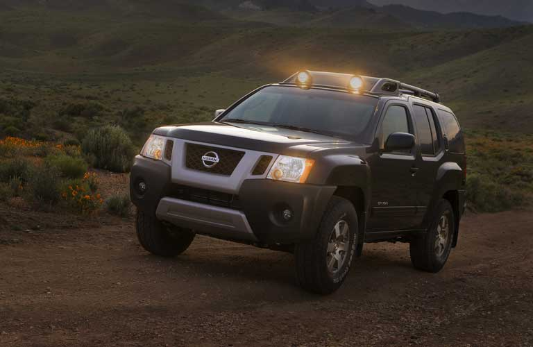 Front driver angle of a black 2009 Nissan Xterra driving off-road