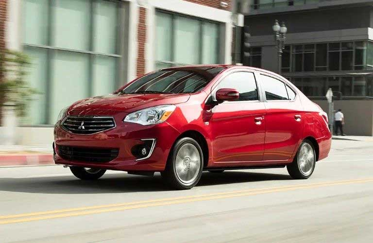 Front driver angle of a red 2019 Mitsubishi Mirage G4 driving down a road