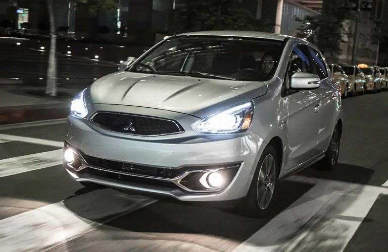 Front driver angle of a silver 2020 Mitsubishi Mirage driving in a city at night