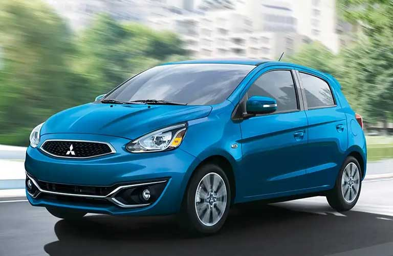 Front driver angle of a blue 2020 Mitsubishi Mirage driving on a road