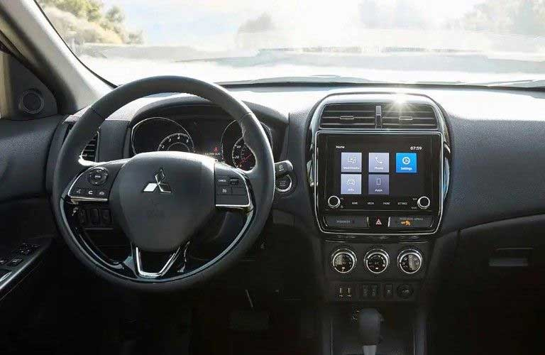 Close up of the steering wheel and touchscreen inside the 2020 Mitsubishi Outlander Sport