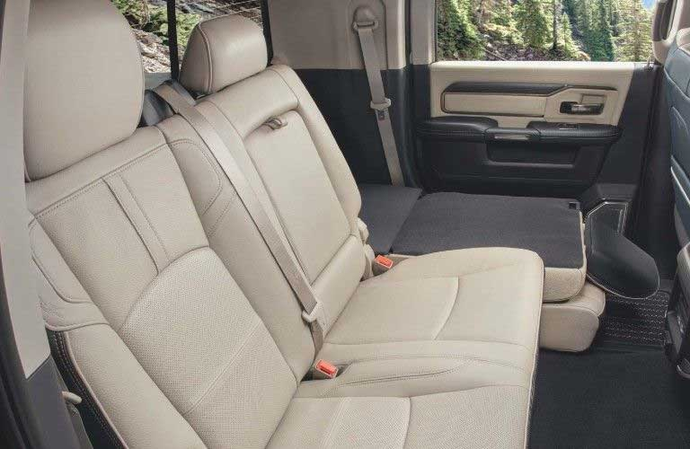 Passenger angle of the rear seats inside the 2020 RAM 3500 with one of them folded down