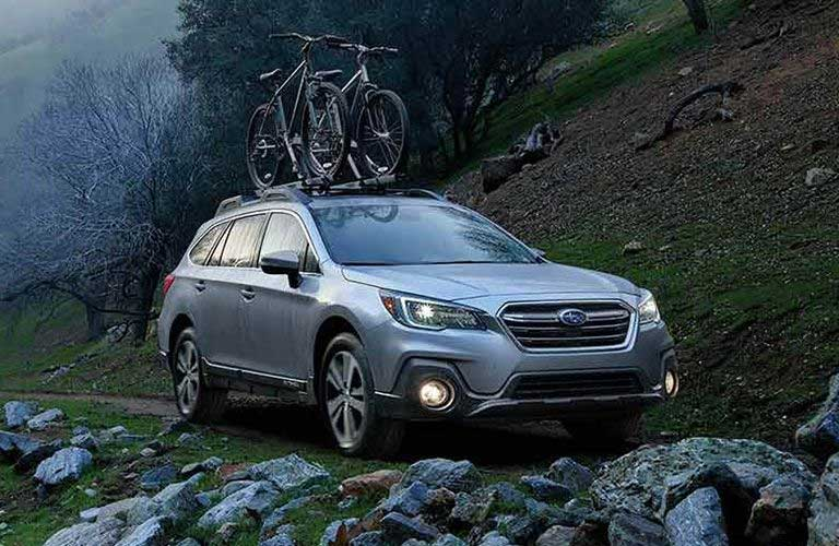 Front passenger angle of a grey 2019 Subaru Outback driving on rocky terrain with bikes loaded on top