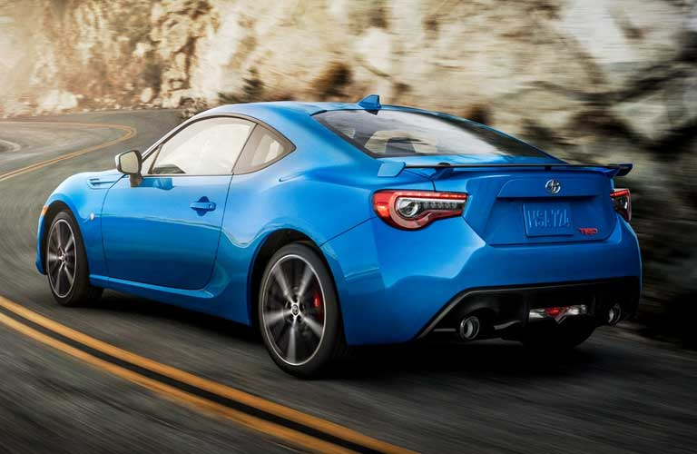 Rear driver angle of a blue 2020 Toyota 86 driving on a road
