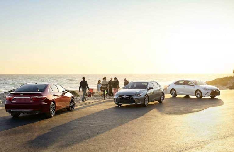 People gathering on a beach near three 2017 Toyota Camry vehicles