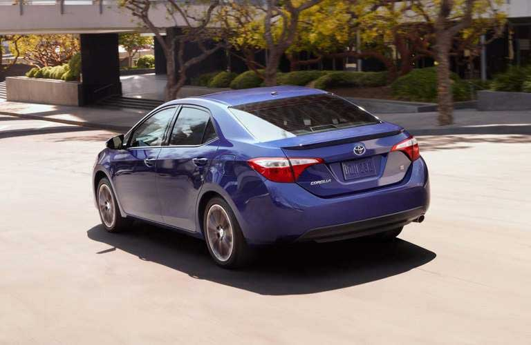 Rear Profile of the 2016 Toyota Corolla driving by a modern building