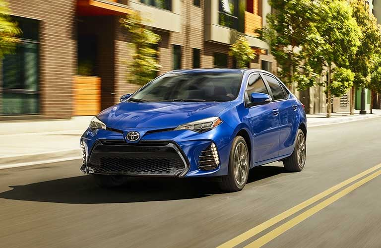 Used 2017 Toyota Corolla driving down an empty street lined with brick buildings