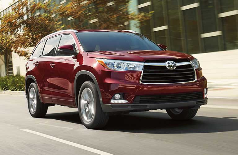 2016 Toyota Highlander driving on a road down town in a city