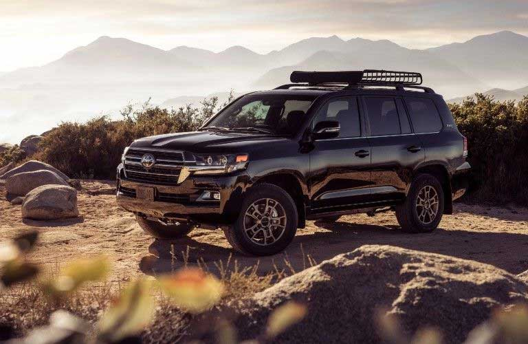 Front driver angle of a black 2021 Toyota Land Cruiser parked in the wilderness