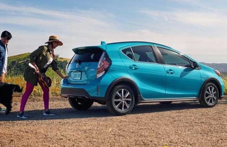 Rear passenger angle of a blue 2019 Toyota Prius c with people and a dog standing near it