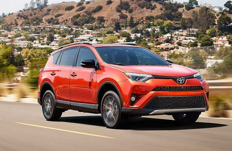 2017 Toyota RAV4 driving by a hilly area with a bunch of houses