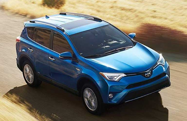 2017 Toyota RAV4 driving on a country road around a corner through a field