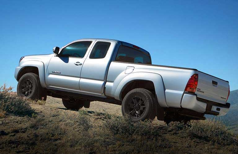 2014 Toyota Tacoma driving up a slight incline in a desert terrain