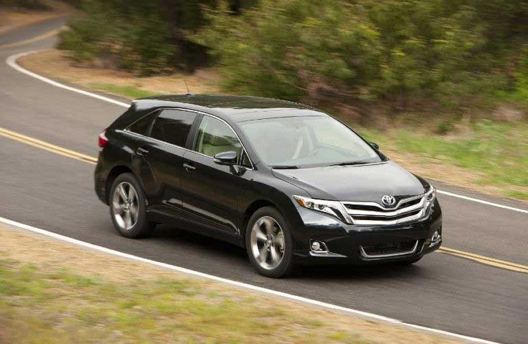 Front passenger angle of a black 2015 Toyota Venza driving on a road