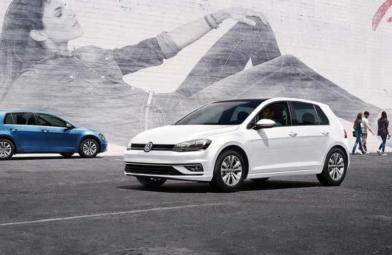 Two Volkswagen Golf hatchbacks parked by each other