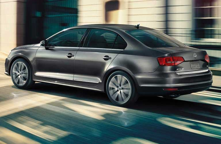 2017 Volkswagen Jetta driving down a street with buildings zooming by
