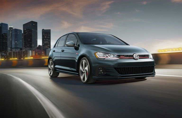 Green 2019 Volkswagen Golf GTI driving away from a city